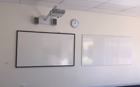 Photo of a TG-850 Ineteractive whiteboard installed next to a standard whiteboard