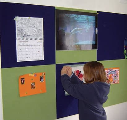 child pinning a drawing to a wall versa-tile